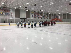 Deux équipes de hockey se remerciant pour leur participation, une fois la partie terminée, au milieu de la glace de l'aréna.