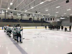 Deux équipes s'opposant sur la glace avant la mise en jeu. Une vêtue de blanc et l'autre vêtue de noir.