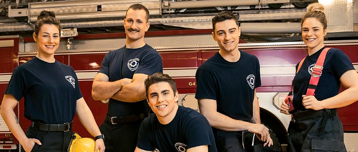 Cinq pompiers en uniforme, trois gars et deux filles, devant un camion de pompier dans une caserne.